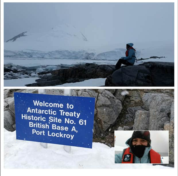 """Guest from a small cruise ship in Antarctica posing by the """"Welcome to Antarctic Treaty Historic Site No. 61 British Base A, Port Lockroy"""" sign."""
