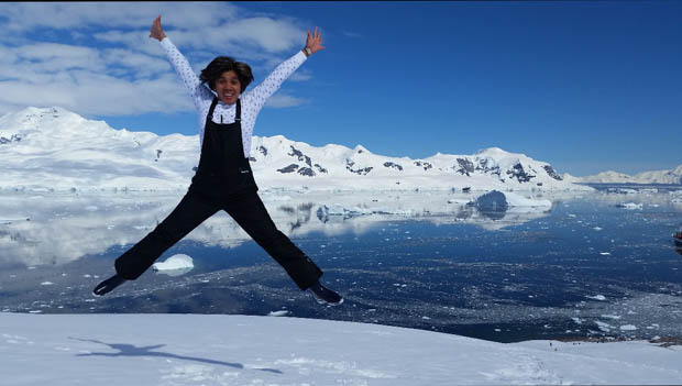 Happy guest from a small ship cruise jumping with arms up in the snow in Antarctica.