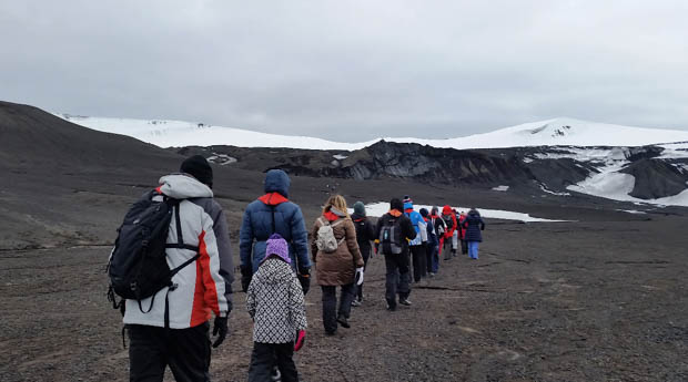 Small ship cruise guests hiking on land in Antarctica.