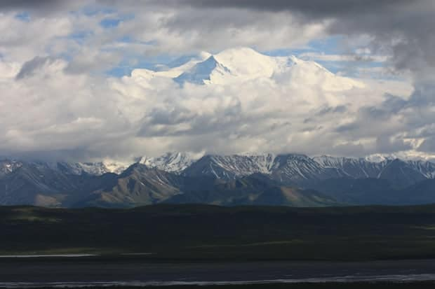 Alaskan mountain range top peaking out from clouds in Denali National Park.