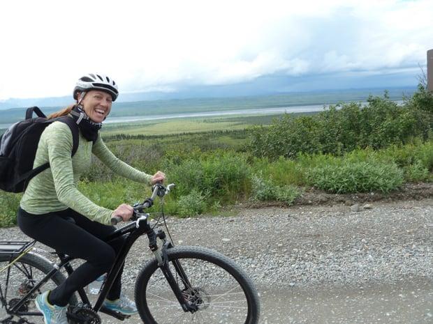 Happy traveler mountain biking on a gravel/dirt road in Denali National Park.