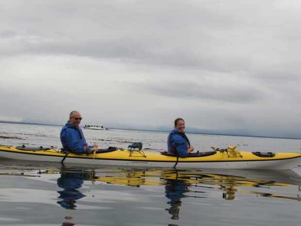 Happy couple sea kayaking in the waters of Icy Strait, Alaska.