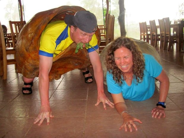 Two laughing people on the ground wearing large tortoise shells.