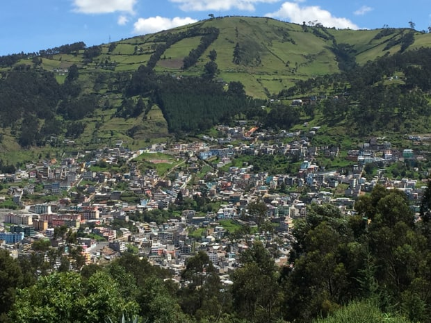 View of a city in Ecuador with green hills in the background.