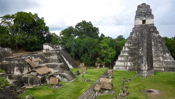 Ancient ruins of Tikal with weathered stone temples rising up from bright green grass, seen during a Guatemala trip.
