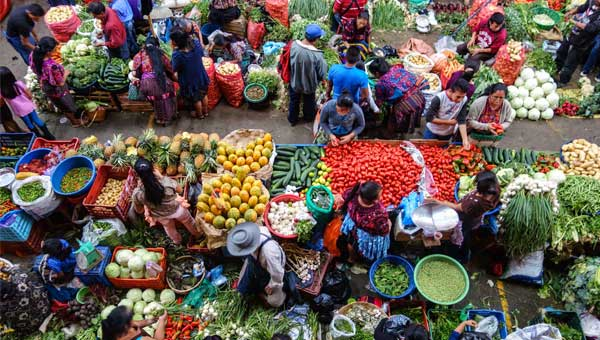 Aerial view of colorful street market showing vendors selling produce, seen during a Guatemala vacation.