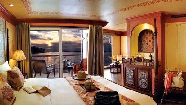 Upscale suite aboard a luxury Southeast Asia tour, with private veranda overlooking a sunset, Moroccan decor, tea service set on a 4-poster bed & a wet bar.