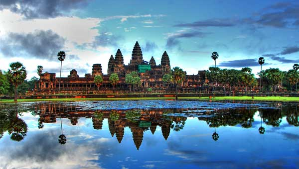 Beautiful temples reflect off of glassy water, surrounded by tall palm trees under a blue sky, on a Southeast Asia vacation.
