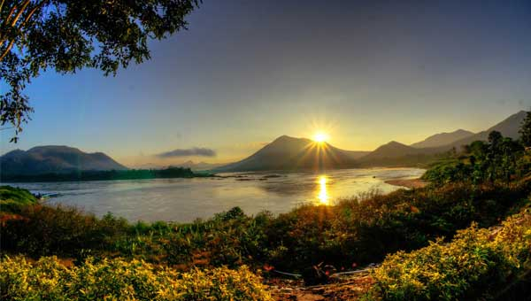 Sun rises above volcanic mountains with bright green bushes in the foreground, seen during a Mekong River cruise.