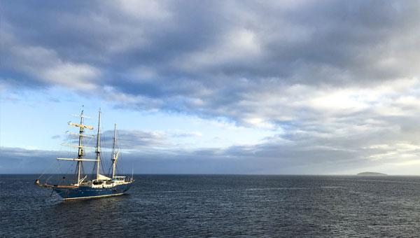 Galapagos sailboat cruises towards the horizon with a cloudy sky at sunset