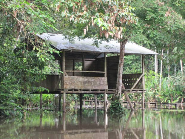 Remote open air hut standing on stilts above water.
