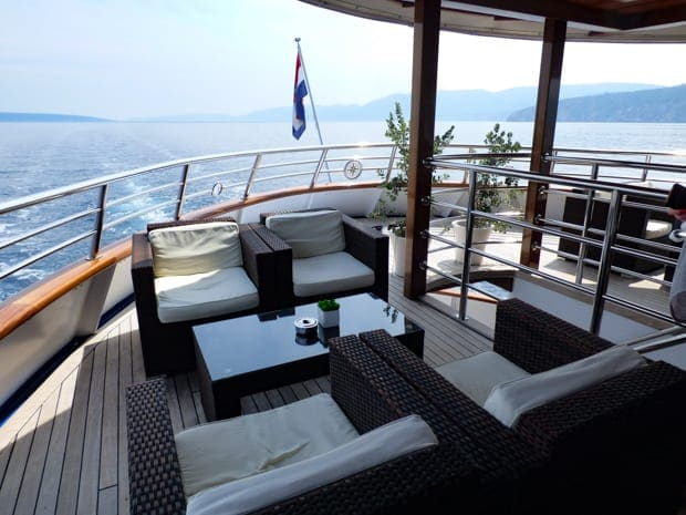 Small ship motor yacht Futura stern side with lounge chairs and tables outside on the deck.