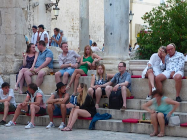 Tourists sitting on steps in Dubrovnik.